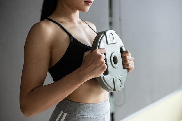 女性は胸にダンベルウェイトプレートを装着して運動します。 無料写真
