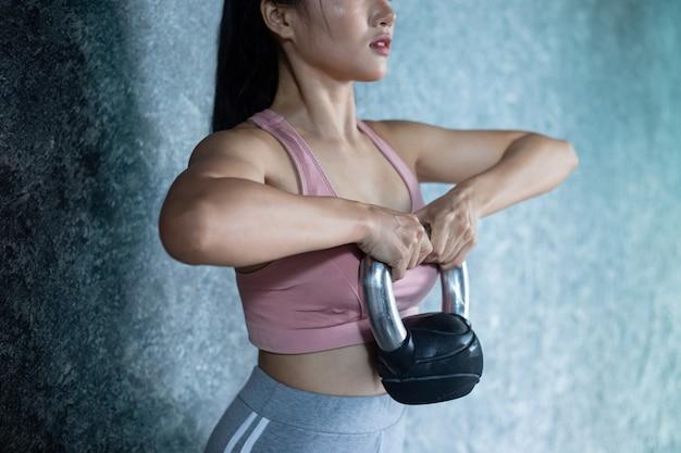 アジアの女の子はジムでケトルベルで運動しています。 無料写真