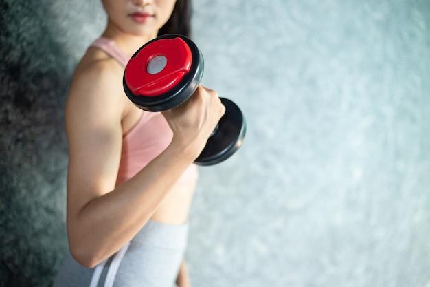 ジムで赤いダンベルで運動に立っている女性。 無料写真