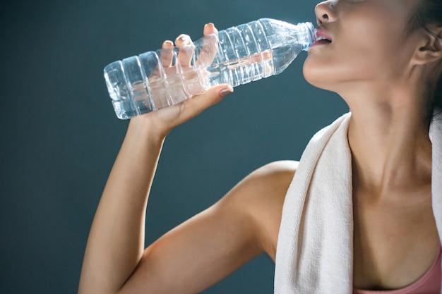 Женщины после тренировки пьют воду из бутылок и носовых платков в спортзале. Бесплатные Фотографии