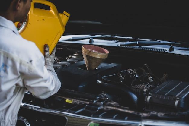 Закройте вверх руку автомеханика лить и заменять свежее масло в двигатель автомобиля в гараже ремонта автомобилей. автосервис и отраслевая концепция Бесплатные Фотографии