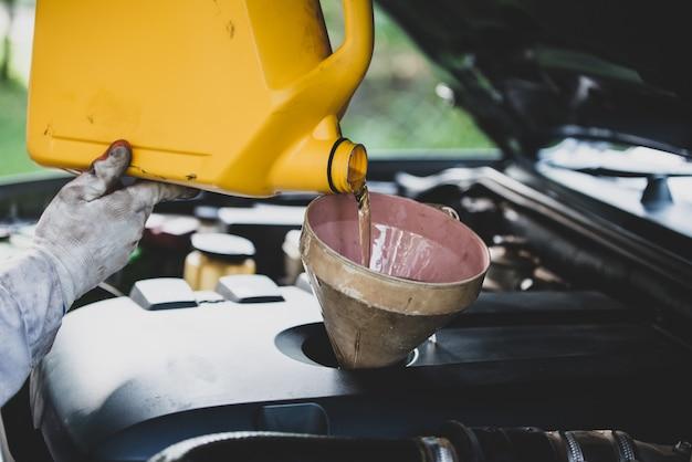 自動車修理工のガレージで車のエンジンに新鮮なオイルを注いで交換する自動車整備士の手を閉じます。自動車整備と産業コンセプト 無料写真
