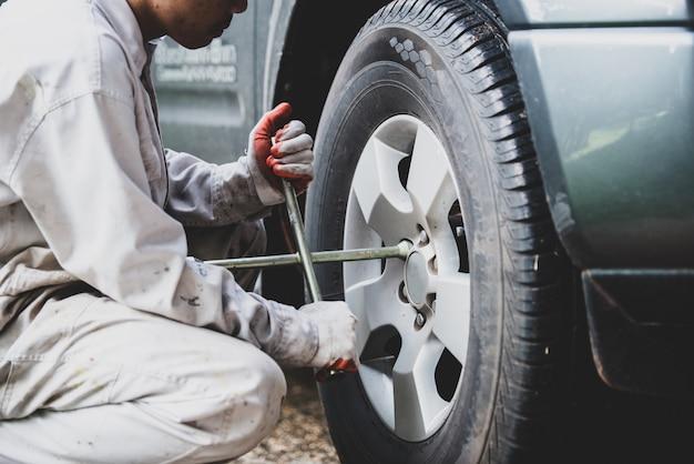 白い制服を着て、メカニックにとって不可欠なツールであるレンチを保持している車の修理工 無料写真