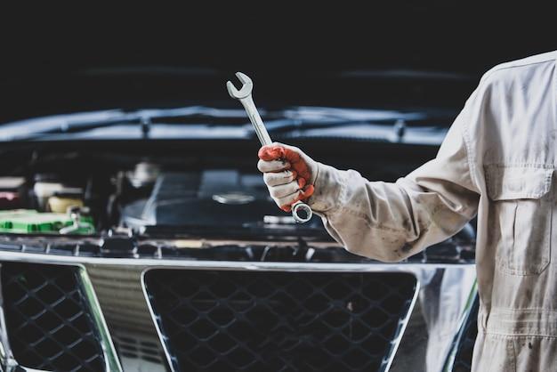Ремонтник автомобиля в белой форме стоит и держит гаечный ключ, который является важным инструментом для механика Бесплатные Фотографии