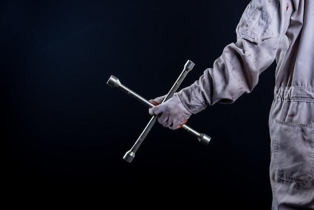Автомеханик в белой форме держит гаечный ключ Бесплатные Фотографии