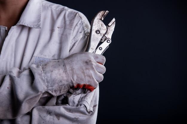 レンチを保持している白い制服スタンドを着て自動車修理工 無料写真