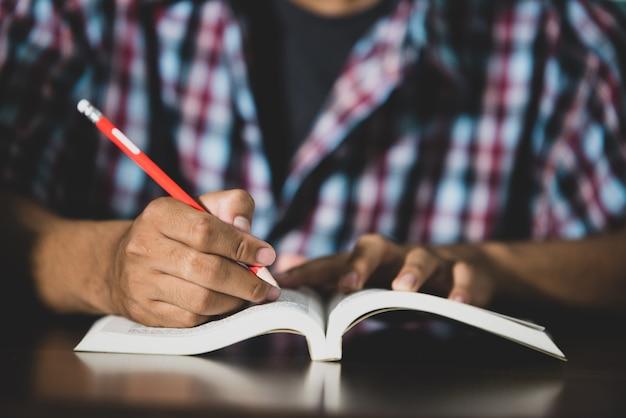 Учебная тема: крупный план. студент пишет в классе. Бесплатные Фотографии