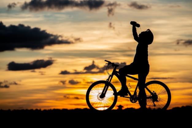 日没時のシルエットを休んでサイクリスト。アクティブな屋外スポーツコンセプト 無料写真