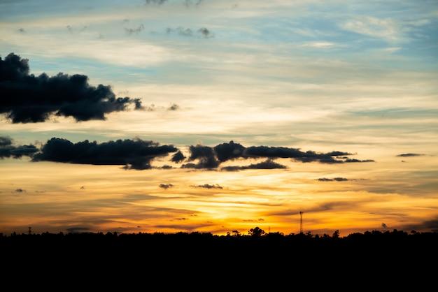 フィールドまたは草原の自然日没の日の出。明るい劇的な空と暗い地面。 無料写真
