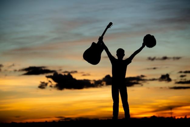 Силуэт девушки-гитариста на закате Бесплатные Фотографии
