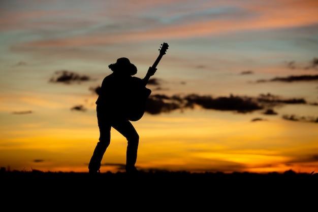 日没のシルエットガールギタリスト 無料写真