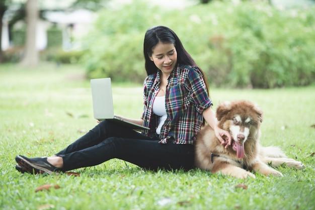 屋外の公園で彼女の小さな犬とラップトップを使用して美しい若い女性。ライフスタイルの肖像画。 無料写真