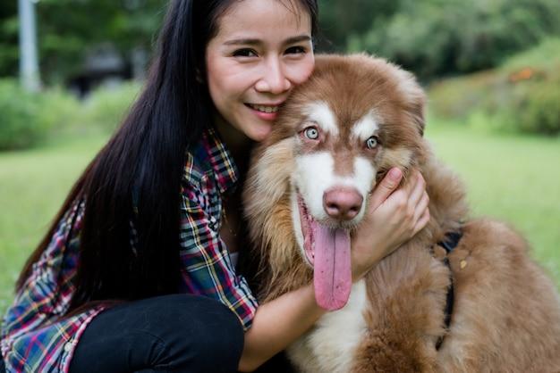 Красивая молодая женщина, играя со своей маленькой собакой в парке на открытом воздухе. образ жизни портрет. Бесплатные Фотографии