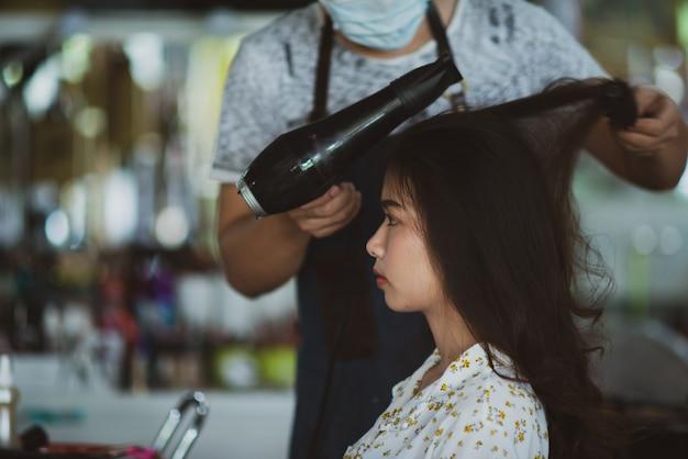 立っている女性の美容師、顔メイクと美容院でかわいい素敵な若い女性に髪型を作る 無料写真