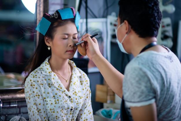 Женский парикмахер, стоя, макияж лица и прическа для милой милой молодой женщины в салоне красоты Бесплатные Фотографии