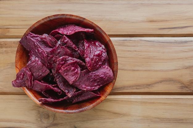 茶色の木製の床に置かれた、カップの紫色のサツマイモ。 無料写真