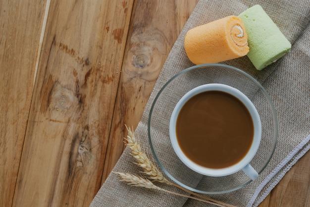 茶色の木の床に置かれたコーヒーとパン。 無料写真