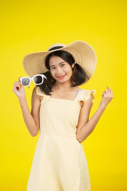 黄色の白いメガネと大きな帽子をかぶっている陽気な美しい女性。 無料写真