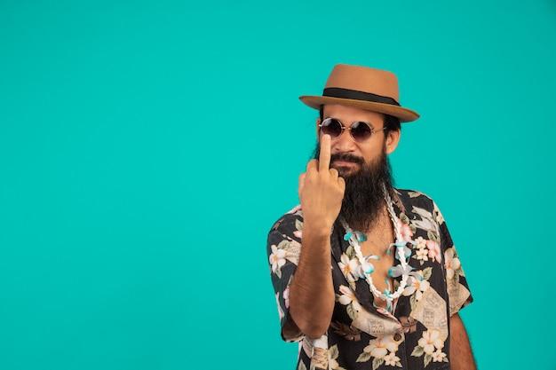 帽子をかぶって、青のジェスチャーを示すストライプのシャツを着て、長いひげを持つ幸せな男の。 無料写真