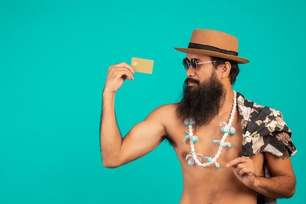 帽子をかぶって、ストライプのシャツを着て、青に金色のクレジットカードを持っている幸せな長いひげ男の。 無料写真