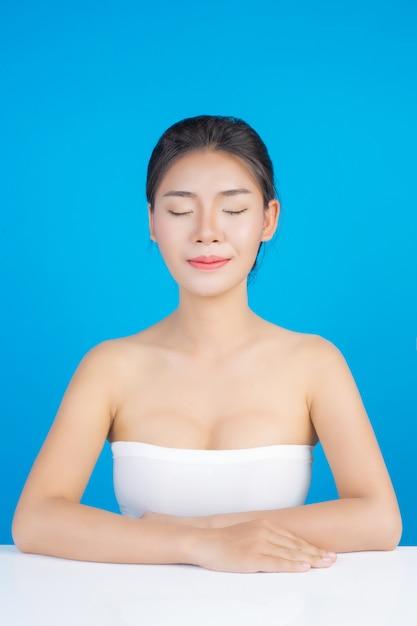 Красота женщины с идеальным здоровьем кожи изображения касаясь ее лица и улыбаясь, как спа, чтобы побаловать ее кожу синий Бесплатные Фотографии