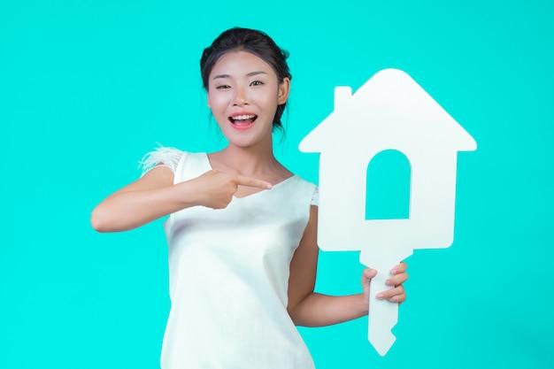 女の子は花柄の白い長袖のシャツを着て、家のシンボルを持ち、青でさまざまなジェスチャーを見せました。 無料写真