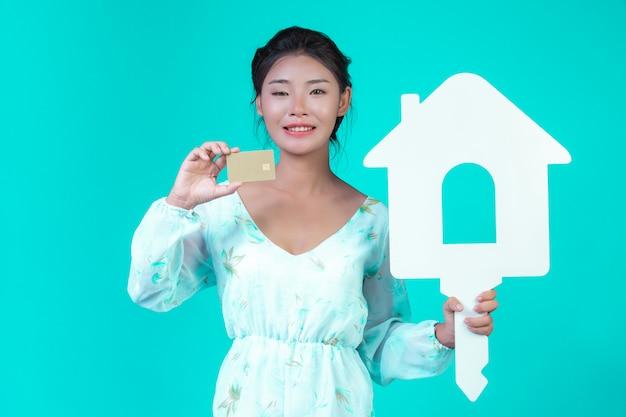 女の子は花柄の白い長袖のシャツを着て、白い家のシンボルと青の金のクレジットカードを持っています。 無料写真