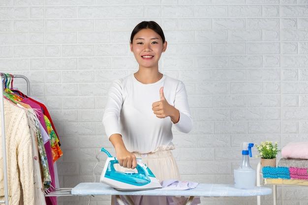 Молодые домохозяйки, использующие утюги, гладят свою одежду на белом кирпиче. Бесплатные Фотографии