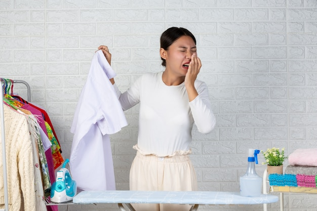 Молодая горничная, которая воняет, пахнет готовой рубашкой на белом кирпиче. Бесплатные Фотографии
