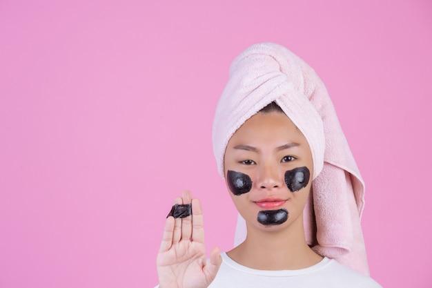 Косметический косметический пилинг. молодая самка с черной отшелушивающей маской на коже косметический уход за кожей пилинг продукт на лице на розовый. Бесплатные Фотографии