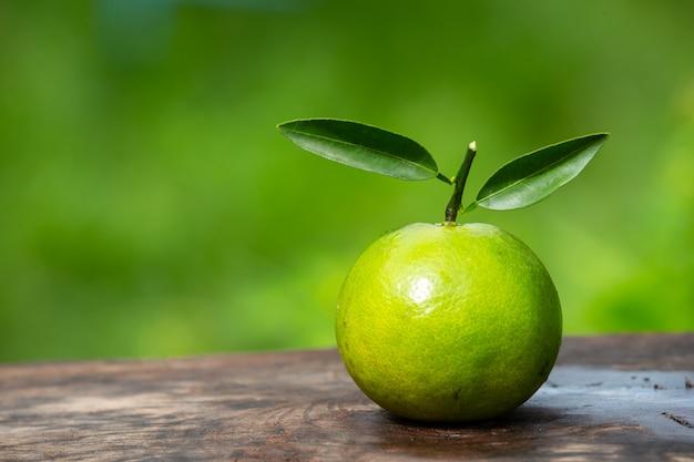 Плод апельсина размещен на деревянном полу и имеет натуральный зеленый цвет. Бесплатные Фотографии
