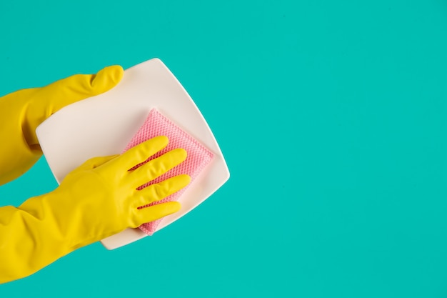 青い皿に黄色の手袋をはめた食器洗い機。 無料写真