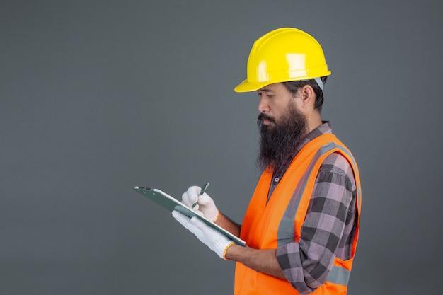 Человек инженерства нося желтый шлем с дизайном на сером цвете. Бесплатные Фотографии