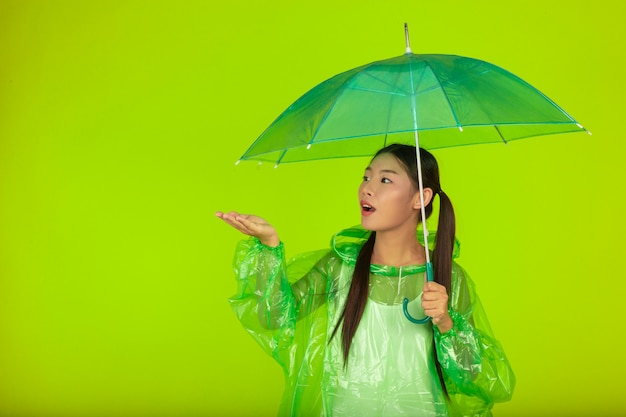 Счастливая красивая девушка, нося зеленую одежду, зонтик и пальто, дождливый день. Бесплатные Фотографии