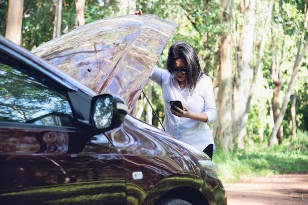 アジアの女性が地元の道路で車のエンジンの問題を解決するために修理や保険のスタッフを呼び出す 無料写真