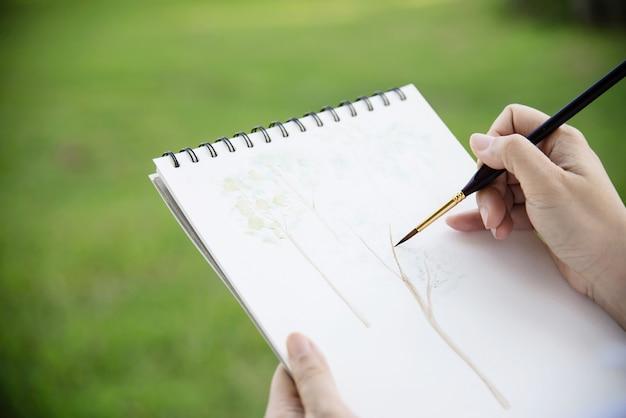 緑の庭の森の自然の中で女性の絵画水彩アート作品をリラックスします。 無料写真