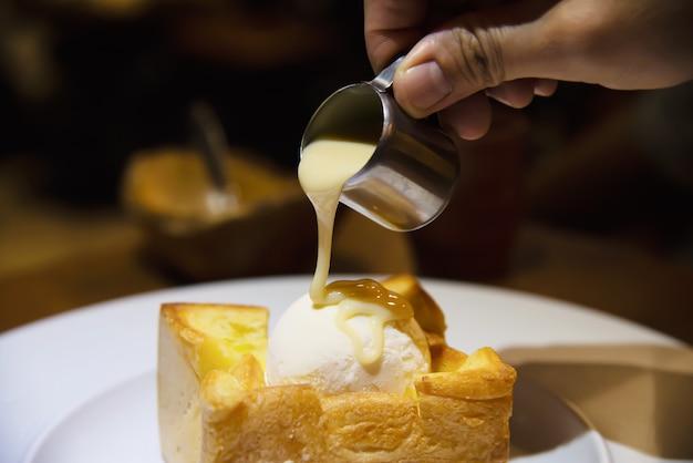 アイスクリームパントーストに牛乳を注ぐ人 無料写真