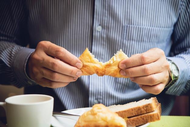 ビジネスの男性はホテルで設定されたアメリカン・ブレックファーストを食べる 無料写真
