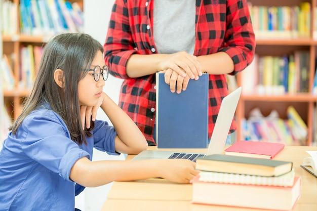 学校の図書館で勉強している学生 無料写真