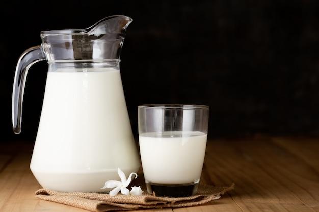 Молоко в стакане и кувшин на деревянный стол Бесплатные Фотографии