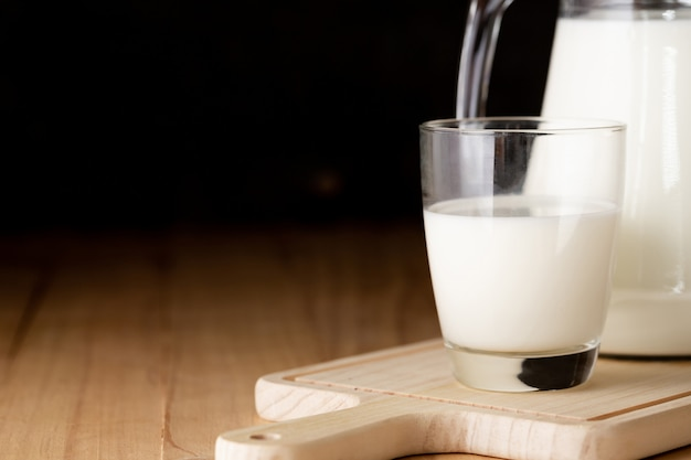 ガラスと木製のテーブルの水差しのミルク 無料写真
