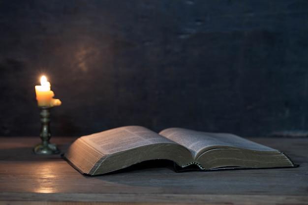 聖書と木製のテーブルの上のろうそく 無料写真
