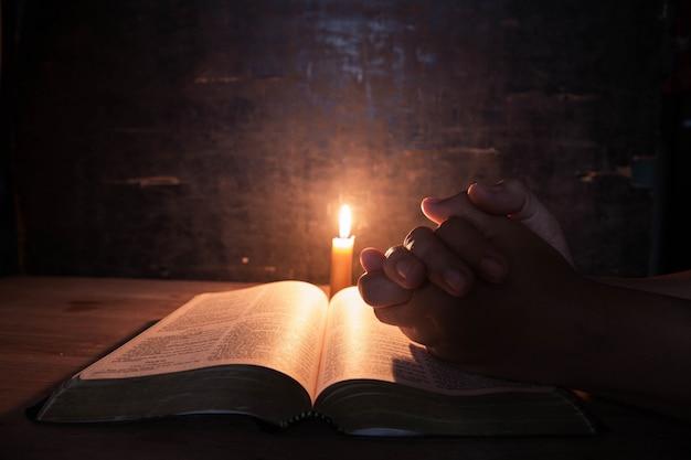 キャンドルのセレクティブフォーカスで聖書に祈る女性。 無料写真