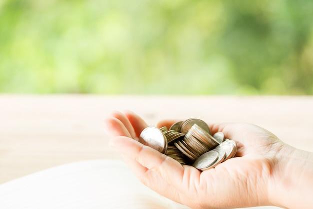 女性の手は多くのコインを保持しています 無料写真