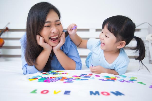 母と娘、アルファベットを勉強 無料写真