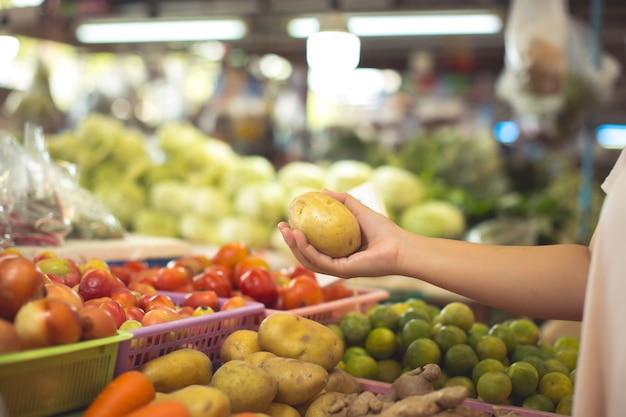 Женщина покупает органические овощи и фрукты Бесплатные Фотографии