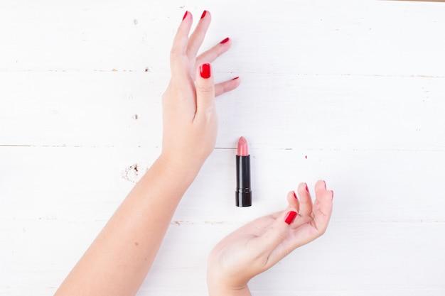 口紅を取っている赤い爪と女性の手 無料写真