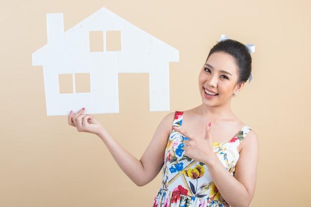 紙の家を保持している若い幸せな興奮したアジア女性の肖像画 無料写真