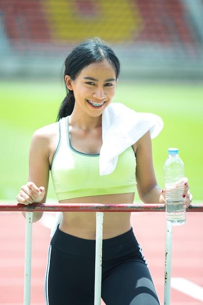 Женщина спортсменка отдыхает и пьет воду Бесплатные Фотографии