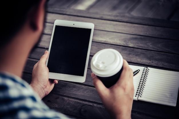若い男は飲みながらデジタルタブレットを使用しています。家庭の庭に座ってコーヒー、朝はリラックスします。 無料写真